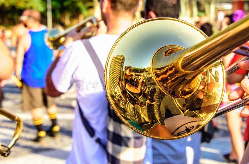Shiny trombone and blurry musicians playing catchy music at Leme district, Rio de Janeiro, Brazil. Shiny trombone and blurry musicians playing catchy music at stock photos