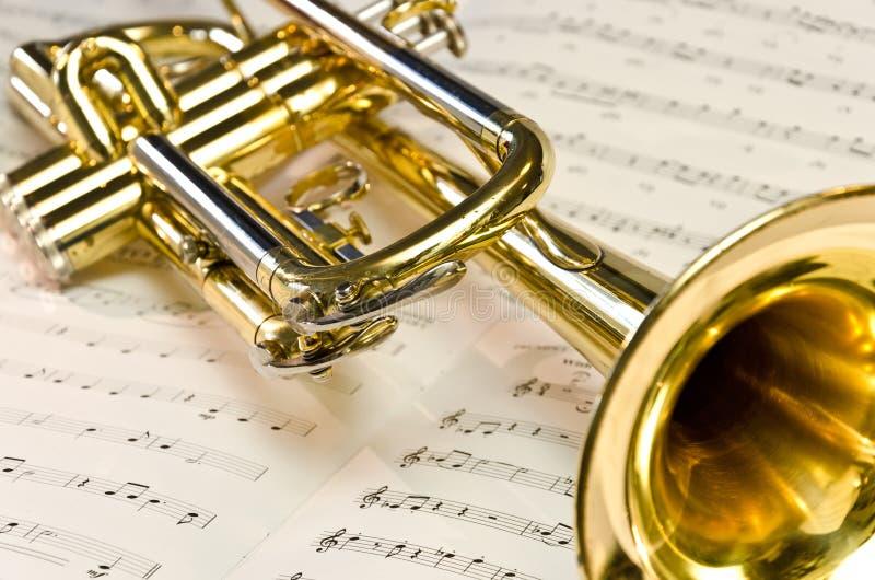 Shiny trumpet on sheet music stock images