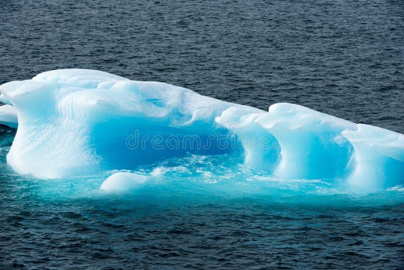 Shiny turquoise Iceberg surrounded by turquoise shiny water, Greenland. Beautiful white and turquoise small iceberg with shiny water and dark blue sea near Disko stock photos