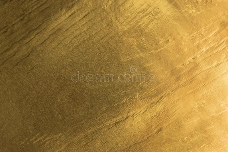 Shiny yellow gold foil texture background with gradient shadow royalty free stock image