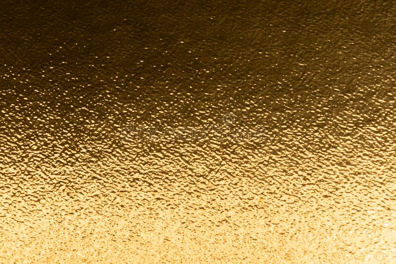 Shiny yellow gold foil texture background with gradient shadow stock photo