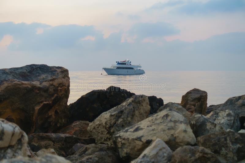 Ship anchored in the dawn sea against  background of rocks stock photo