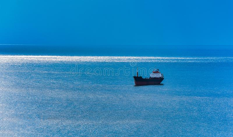 Ship on the blue sea. A ray of sunshine close to the horizon line royalty free stock photo