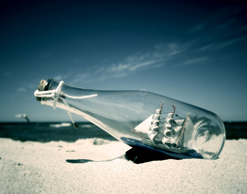 Ship in the bottle. Bottle with ship inside lying on the beach. Conceptual image stock images
