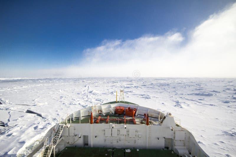 Ship breaking ice at the frozen ocean of Antarctica stock photography