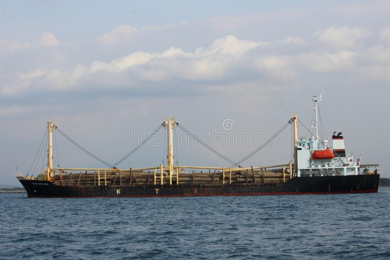SHIP BRINGS WOOD. IN MAYANGAN BEACH stock photography