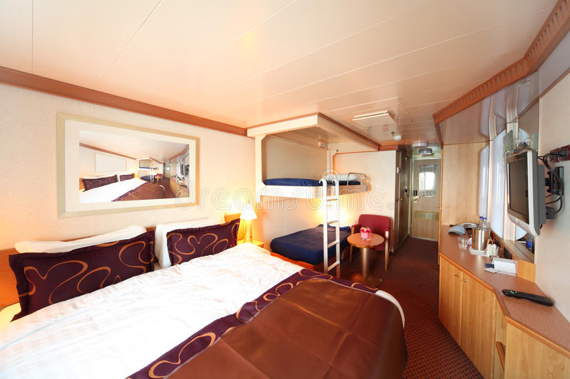 Ship cabin with bed and two children beds stock photos