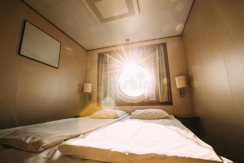 Ship Cabin With Bed And Window With View On Sea. Luxury Cabin On Ferry Boat Or Cruise Liner. Sunset Sun Shine Through royalty free stock photos