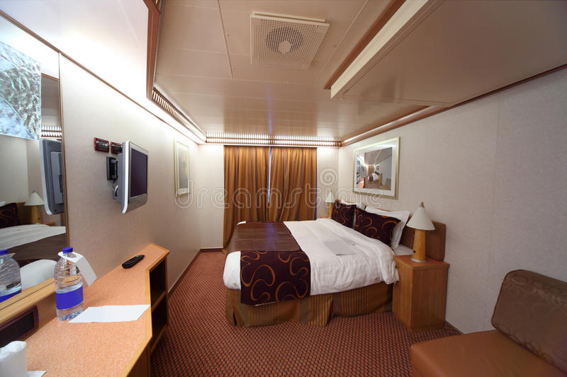 Ship cabin with double bed and curtain on window royalty free stock photo