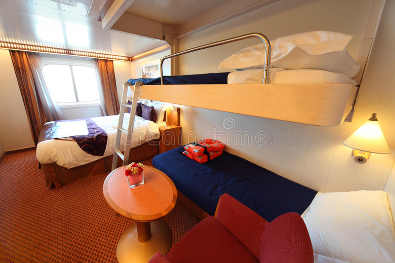 Ship cabin with window, bed and two children beds stock image