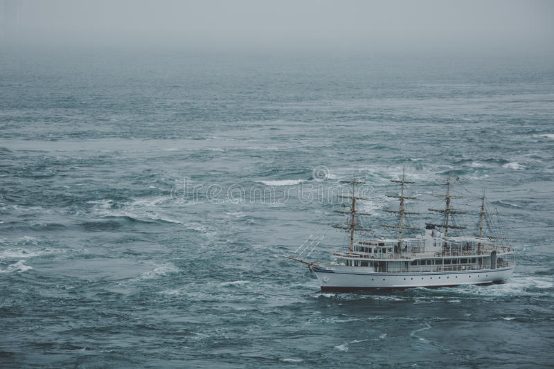 A ship that crosses the sea through a maelstrom stock photography