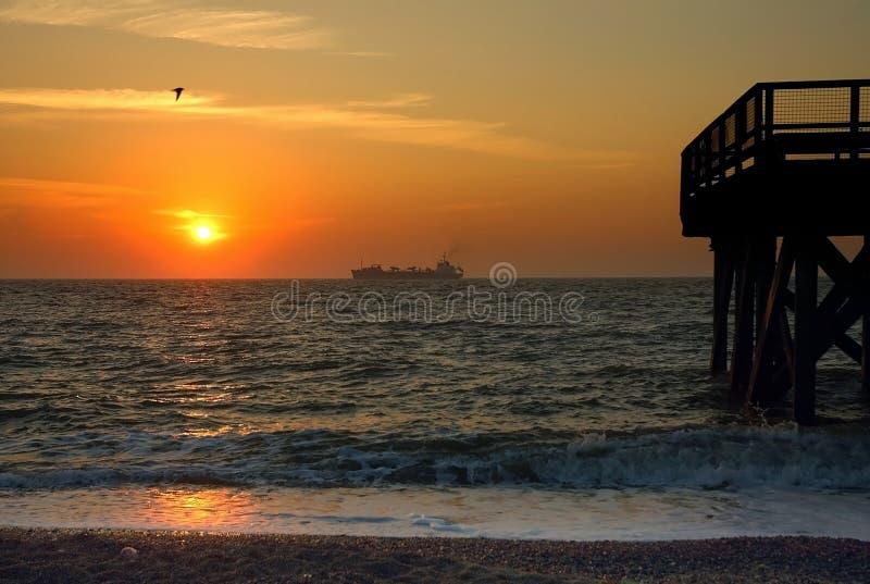 Ship crossing sea at Great Yarmouth sunrise stock image