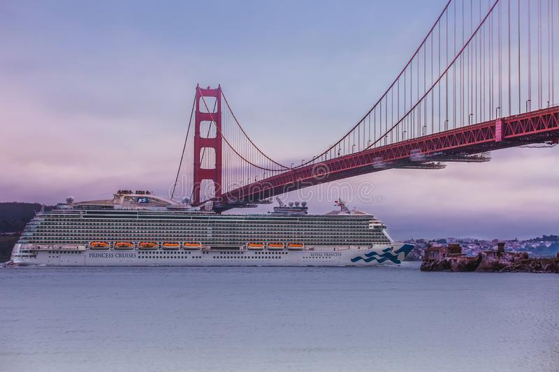 A crusie ship headed out to sea under the goldengate bridge stock photography