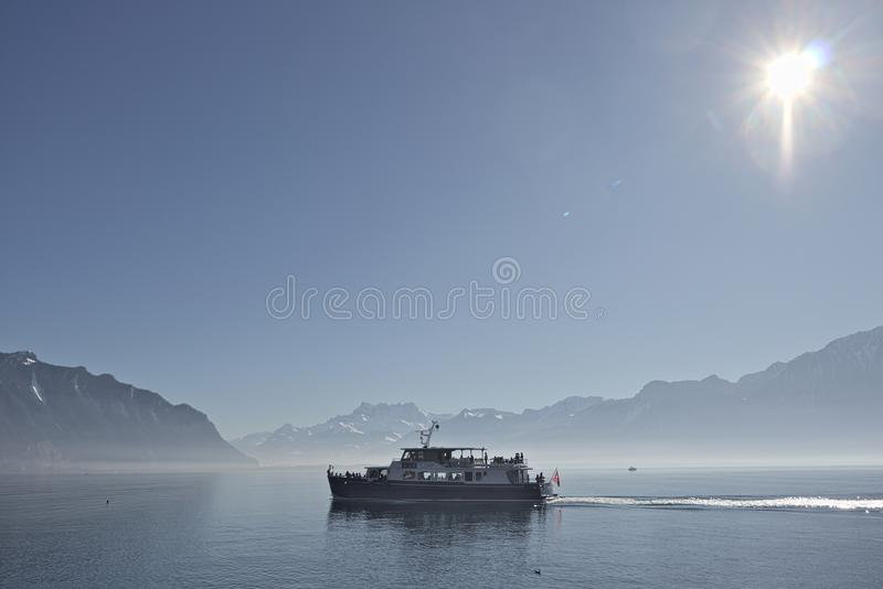 Ship cruising through lake geneva in montreux with mountains in the background. Montreux, Switzerland - 02 17, 2019: Ship cruising through lake geneva in stock photography