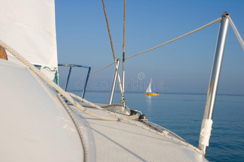 Ship deck. Sailing boat ship deck and a lake view with a yellow sailboat royalty free stock images