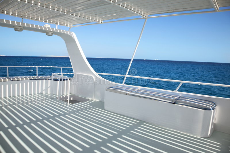 Ship deck. With striped shadowon on blue sea background royalty free stock image