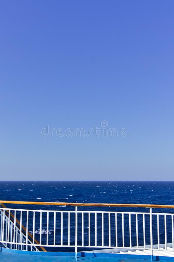 Ship deck railing  while sailing on open sea. Vivid blue color with copy space. Ship deck curved railing  while sailing on open sea. Vivid blue color with copy stock photos
