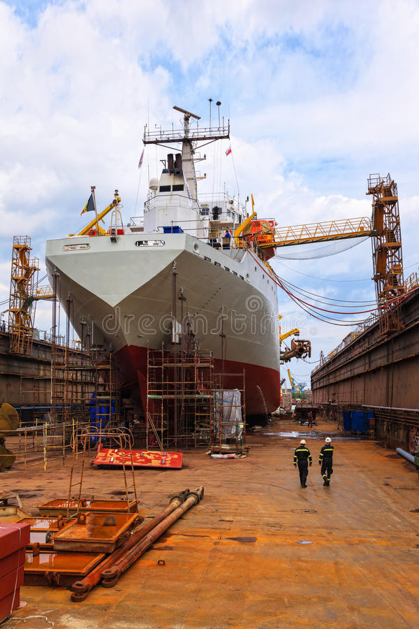A ship in a dry dock. A large cargo ship is being renovated in shipyard Gdansk, Poland royalty free stock photo