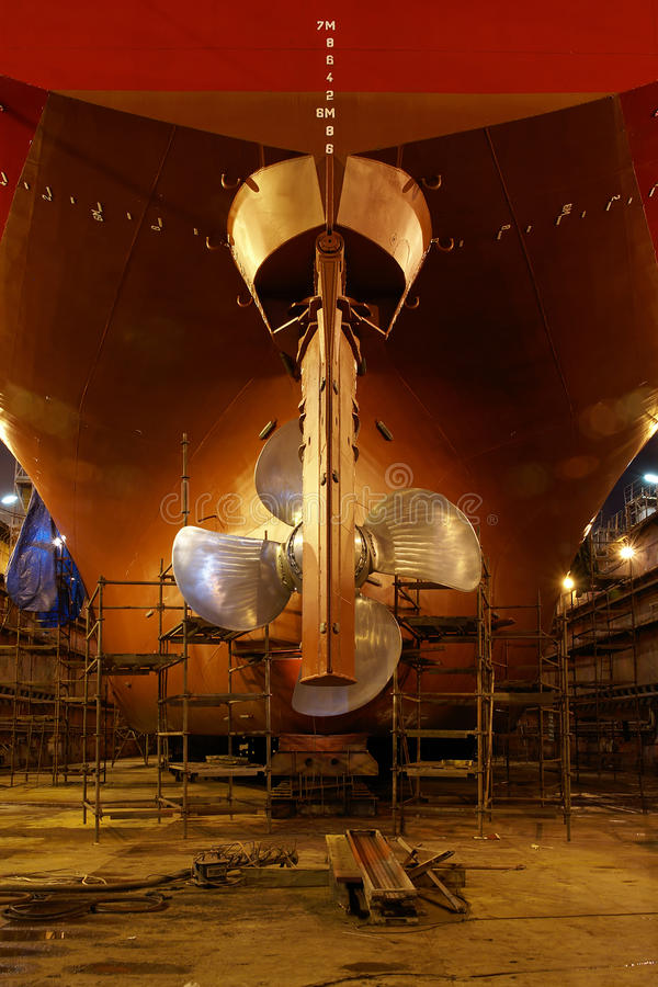 Ship in dry dock. The hull and propeller of a large ship in a dry dock being prepared for maintenance and repair work stock image
