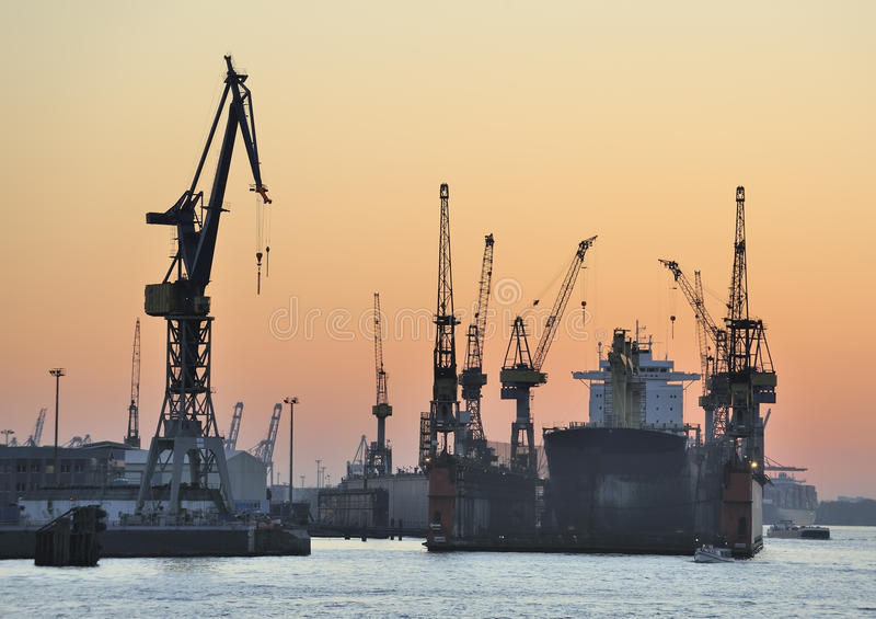 Ship in dry-dock and cranes at sunset stock images