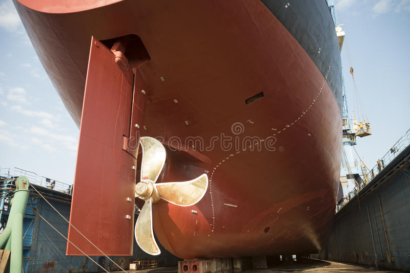 Ship in dry dock. The hull and propeller of a vessel in a dry dock being prepared for maintenance and repair works stock photo