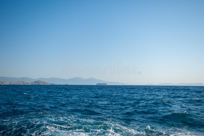 A ship far into the sea, carrying tourists stock photography