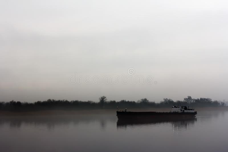 Ship on the IJssel river near Wilsum during a early sunny and misty morning. royalty free stock photos