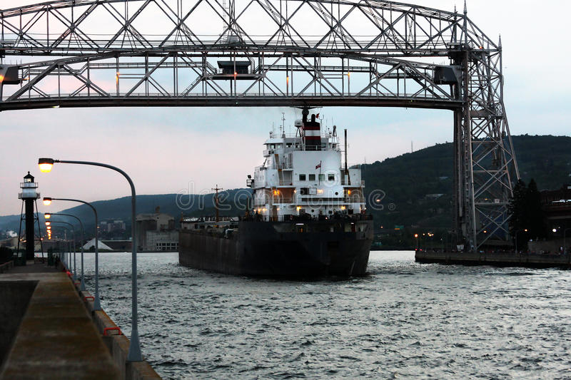 Empty container ship entering Duluth harbor. An empty iron ore and taconite container ship crosses under a vertical lift bridge, entering Duluth harbor at dusk stock photography
