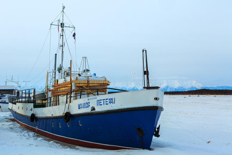 Ship in frozen lake covered with snow in winter evening royalty free stock photos