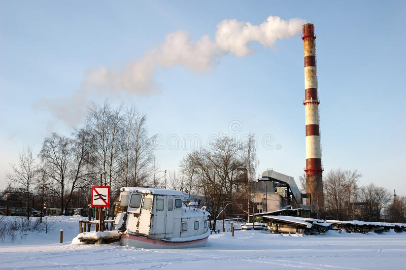 Ship on frozen river with traffic sign and chimney. Old Ship on frozen river with traffic sign and chimney stock photography
