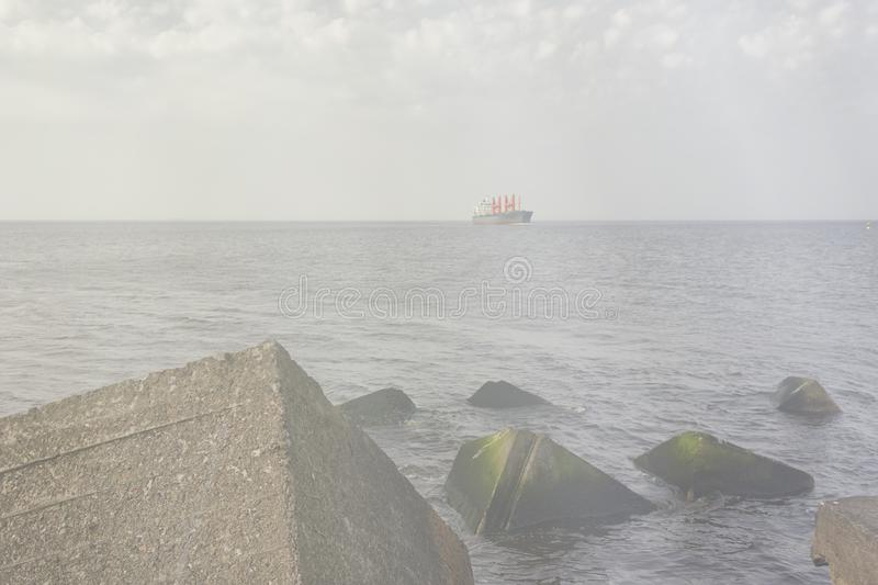 The ship goes along the horizon line. A merchant ship walks along the horizon line of the Baltic Sea against the backdrop of storms on the shore royalty free stock image