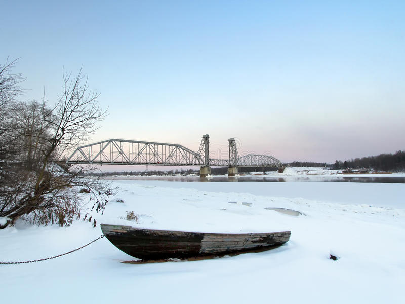 Ship mans boat on the beach at winter sunset with the train bridge on a background stock photo