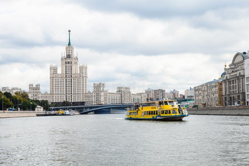 Ship on Moskva River and High-Rise Building. MOSCOW, RUSSIA - SEPTEMBER 16, 2017: view of excursion ship on Moskva River near Bolshoy Ustinsky Bridge and stock photo