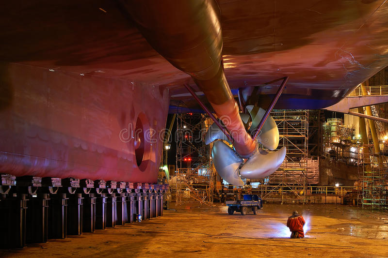 Ship repair. A welder works at night beneath a massive ship in a dry dock at a shipyard stock photo