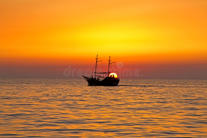 Ship of the rising sun. The ship sails on the sea at dawn in the rays of the rising sun in the background of the solar disk. The sun's rays are reflected in the stock photo