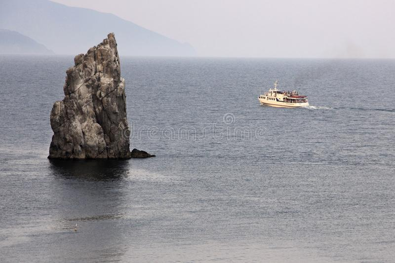 Ship and rock in Crimea. Ship and rock in the black sea royalty free stock images