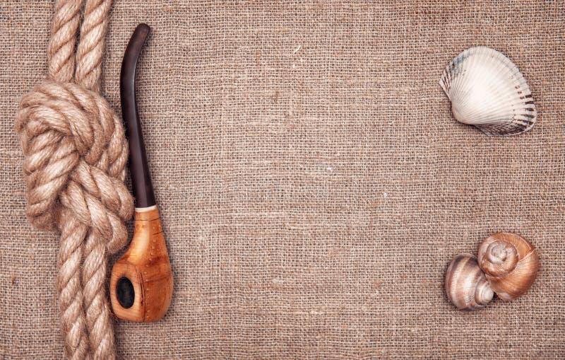 Ship rope, seashells and tobacco pipe royalty free stock photos