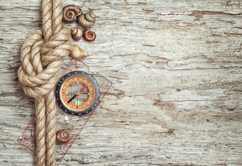 Ship rope, shells, compass and wood background stock image