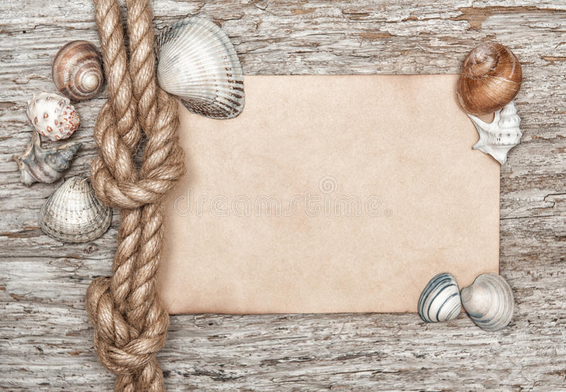 Ship rope, shells, sheet of paper and old wood stock photography