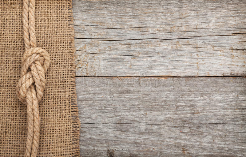 Ship rope on wood and burlap texture background stock photo