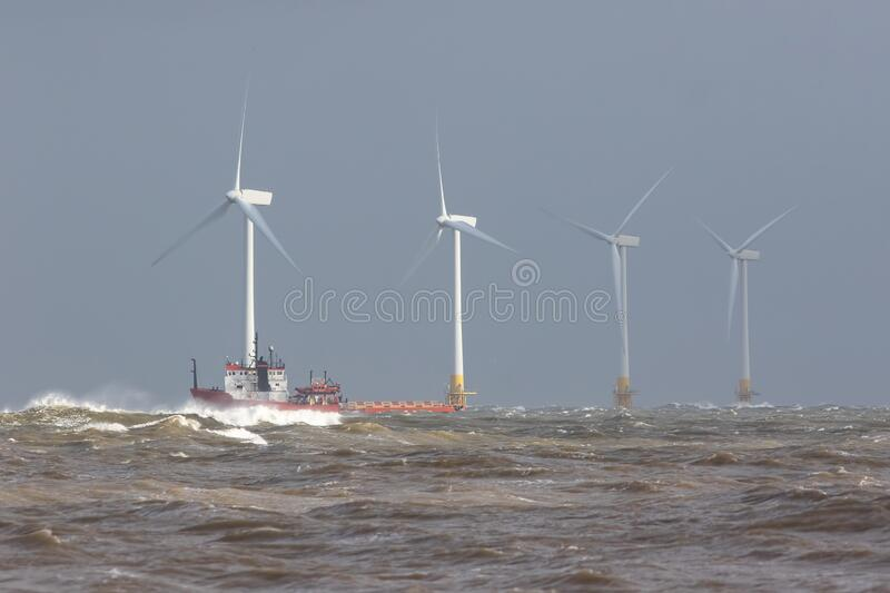 Ship on rough sea horizon by offshore wind farm turbines stock images