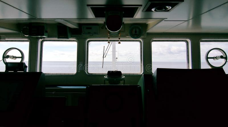 Silhouette of the ship`s bridge with sea and sky infront of the windows. stock photography