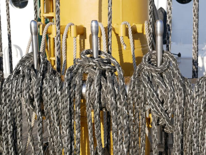 The ship`s rope hangs on the mast of a sailing ship.  A Bay of nylon rope on the deck of a sailboat. stock photography