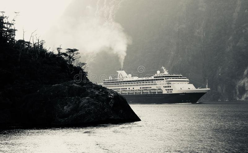 CRUISE SHIP NAVIGATES THE STEEP CLIFFS OF MILFORD SOUND NEW ZEALAND. The ship`s steam mixes with the morning fog as it navigates out of Milford and into the stock image