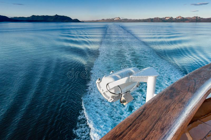Ship`s wake and auxilliary light in the cool clear air of dawn, Alaska, USA. Ship`s wake and white metal exterior auxilliary lamp in the cool clear air of early royalty free stock images