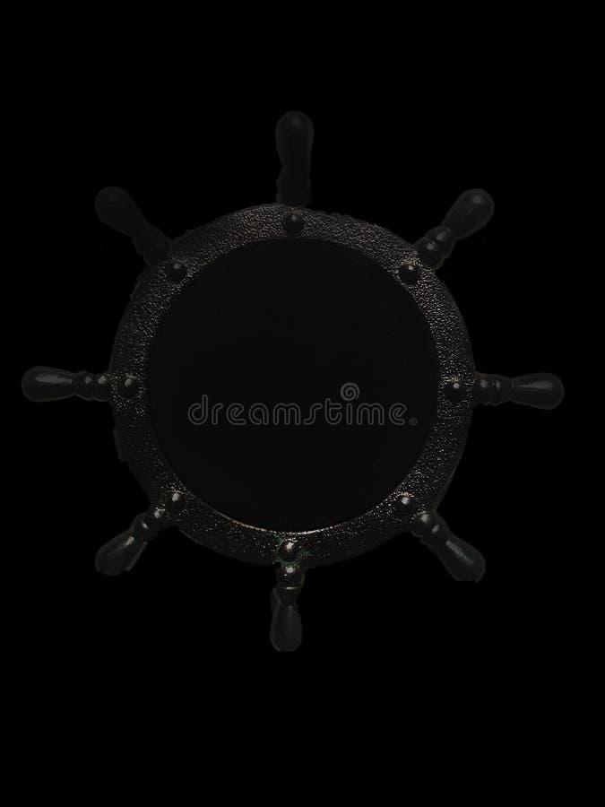The ship`s wheel on a black background stock photos