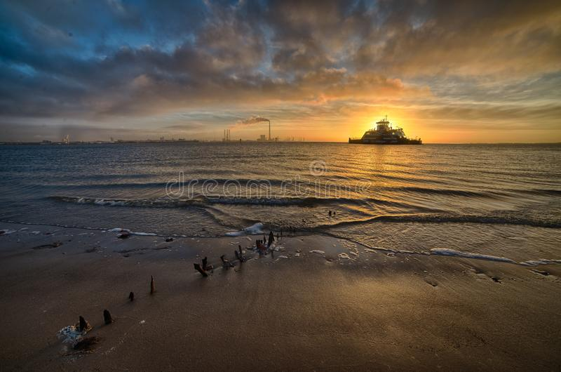 Ship sailing over the sea during a breathtaking sunset under the cloudy sky stock photography