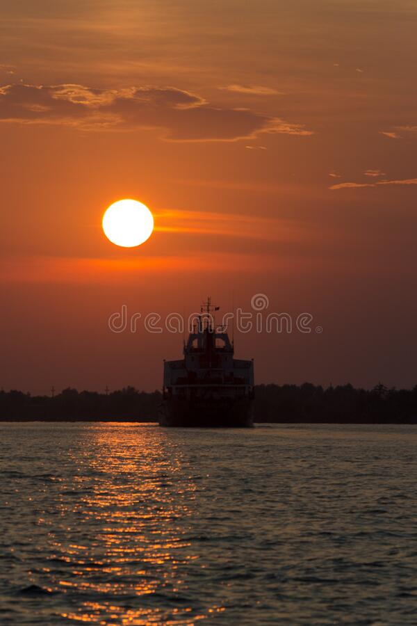 ship sailing into sunset stock images