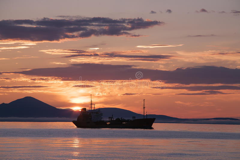 The ship in the sea against the backdrop of the rising sun. The Sea of Okhotsk. Magadan Region. Russia royalty free stock image