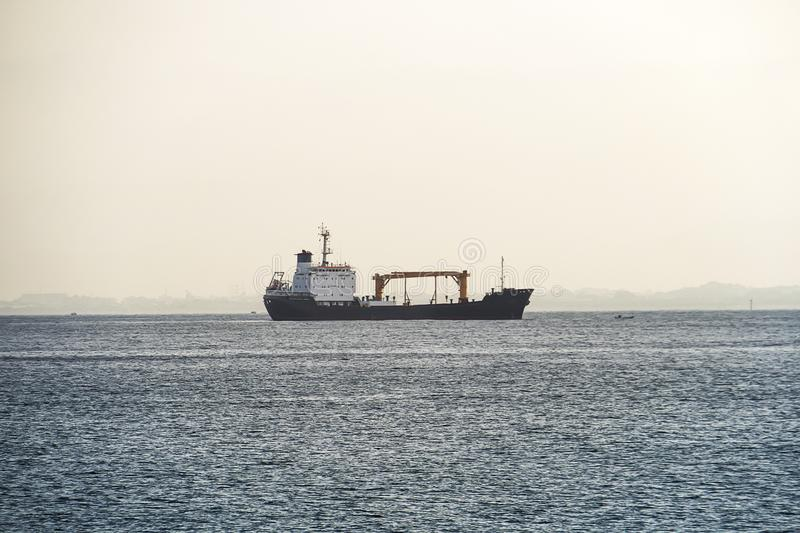 Ship in the sea, Freight Transportation, Shipping, Nautical Vessel. Ship appering on the sea horizon. Logistic and navigation royalty free stock image